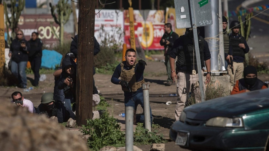 Jan. 7, 2017: Mexican police take cover with guns drawn and pointed towards protesters who were blocking a fuel facility in Rosarito, near Tijuana, Mexico.