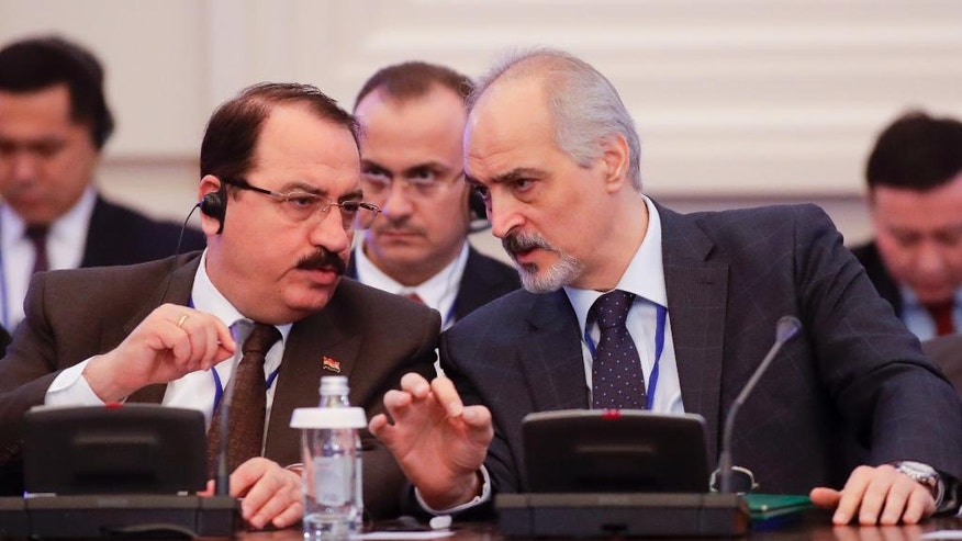 Bashar Jaafari, Syrian Ambassador to the UN and head of the Syrian delegation, right, speaks to a member of Syrian delegation during the talks on Syrian peace in Astana, Kazakhstan, Monday, Jan. 23, 2017. Syria talks brokered by Russia, Turkey and Iran aimed at bolstering a shaky cease-fire in place since last month opened on Monday in Kazakhstan, marking the first face-to-face meeting between the Damascus government representatives and rebel factions trying to overthrow it. The gathering is also the start of a new effort to end six years of carnage that has killed hundreds of thousands, displaced half of Syria's population and sent millions of refugees to neighboring countries and Europe. (AP Photo/Sergei Grits)
