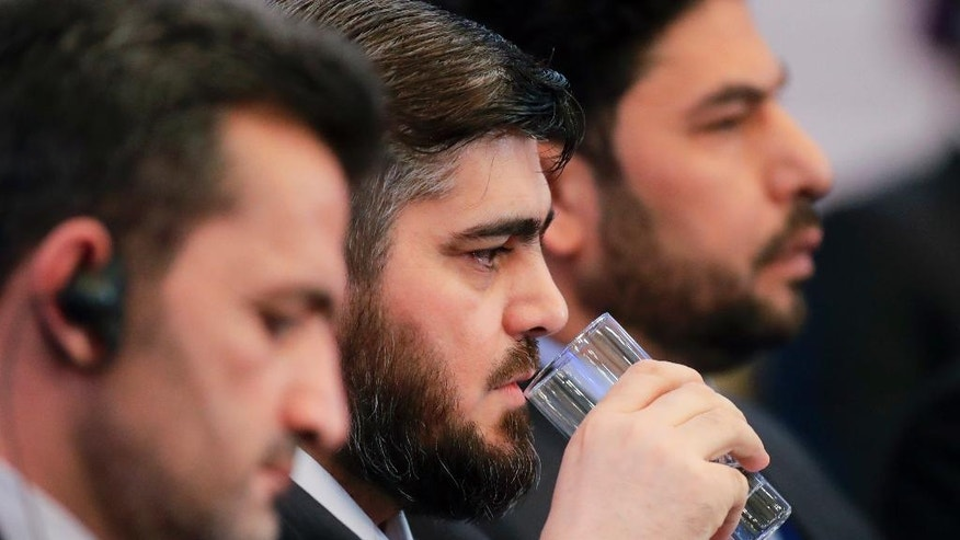 Mohammed Alloush, head of Syrian opposition delegation, drinks water during  talks on Syrian peace in Astana, Kazakhstan, Monday, Jan. 23, 2017. The talks are the latest attempt to forge a political settlement to end a war that has by most estimates killed more than 400,000 people since March 2011 and displaced more than half the country's population. (AP Photo/Sergei Grits)