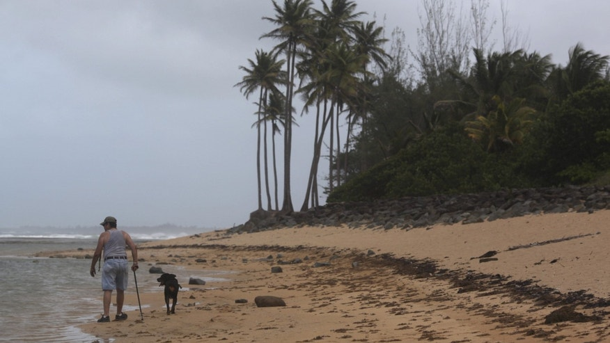 A man walks with his dog on the beach in San Juan, Puerto Rico.