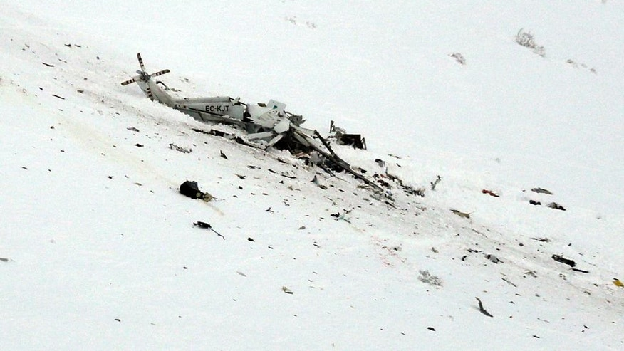 The wreckage of an helicopter lies in the snow after crashing in the Campo Felice ski area, central Italy, Tuesday, Jan. 24, 2017. A helicopter ferrying an injured skier off the slopes crashed Tuesday in central Italy with at least six people aboard, another tragedy to hit a region slammed by recent earthquakes, heavy snowfall and an avalanche. (AP Photo/Gregorio Borgia)