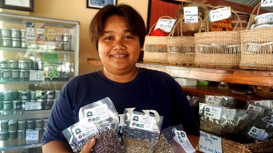 In the Nov. 23, 2016 photo, Sorn Sothy poses with some of her products at her plantation in Kampot, Cambodia. Lauded by celebrity chefs, exorbitantly priced, Cambodia's Kampot pepper is enjoying a renaissance, aided by special recognition and protection from the European Union in 2016. (AP Photo/Denis Gray)