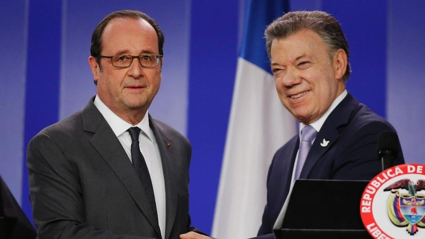 French President Francois Hollande, left, shakes hands with Colombia's President Juan Manuel Santos, at the end of a joint press conference at the Presidential Palace in Bogota, Colombia, Monday, Jan. 23, 2017. Hollande is on a final Latin America tour before stepping down in a few months after elections to choose his successor. (AP Photo/Fernando Vergara)