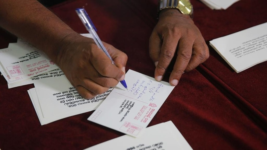 A Sri Lankan media rights activist signs a postcard addressed to president Maithripala Sirisena during a petition signing demanding that Sirisena appoint a presidential commission to investigate all abductions during the country's brutal, decades-long civil war, in Colombo, Sri Lanka, Tuesday, Jan. 24, 2017. One of Sirisena's campaign promises was to end the culture of impunity that allowed those excesses to continue unchecked but two years later there is little sign that the suspects, mostly government military soldiers would face punishment. (AP Photo/Eranga Jayawardena)