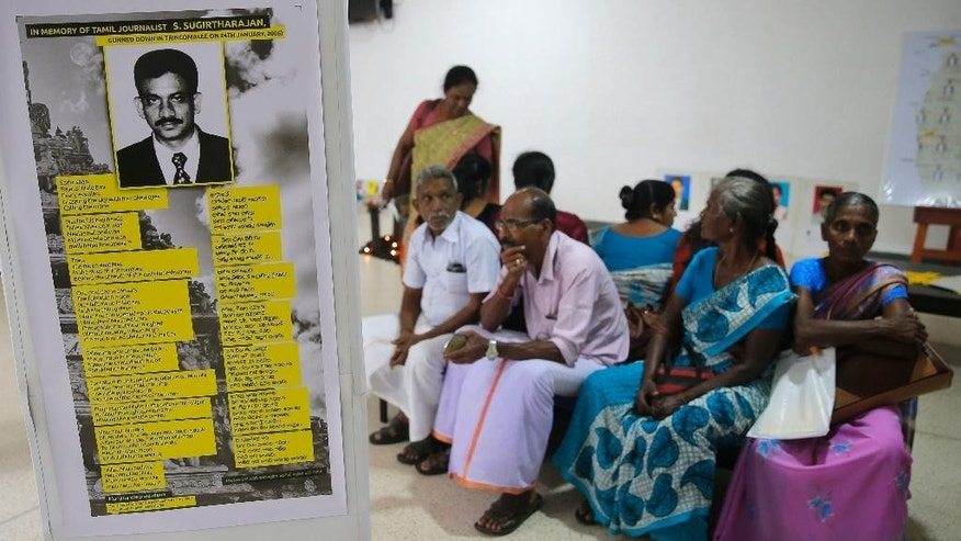 A poster showing a portrait of slain ethnic Tamil journalist S. Sugirtharajan is pasted on a wall as people await to place their signatures during a petition signing demanding that Sirisena appoint a presidential commission to investigate all abductions during the country's brutal, decades-long civil war, in Colombo, Sri Lanka, Tuesday, Jan. 24, 2017. One of Sirisena's campaign promises was to end the culture of impunity that allowed those excesses to continue unchecked but two years later there is little sign that the suspects, mostly government military soldiers would face punishment. Activists and relatives say hope is fading fast for the new Sri Lankan government to act against the perpetrators in the killings and disappearances of journalists during the long civil war or the country's previous administration.(AP Photo/Eranga Jayawardena)
