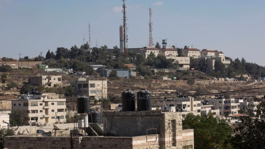 Oct. 24, 2016: This photo shows part of the Israeli settlement of Psagot, background, overlooking Palestinian houses, in a suburb of the West Bank city of Ramallah.