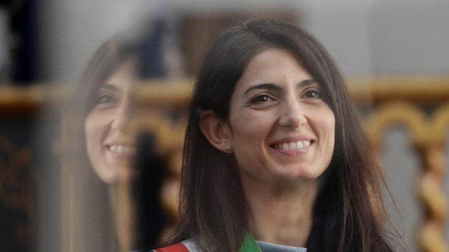 FILE- In this Thursday, Nov. 3, 2016 file photo, Rome's mayor Virginia Raggi is reflected on a panel as she visits the Pope Pius IX train during the opening of its exhibition, in Rome. Prosecutors are seeking to question Rome's embattled mayor over one of several problematic appointments that have tarnished her young administration and Italy's populist 5-Star Movement. (AP Photo/Alessandra Tarantino, File)
