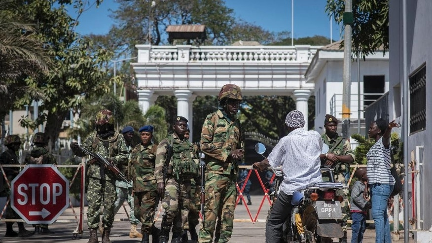 Senegalese soldiers check a motorcyclist at the entrance of the State House compound in Banjul, Gambia, Tuesday Jan. 24, 2017. ECOWAS troops have moved into the State House to prepare for the return of President Adama Barrow. (AP Photo/Sylvain Cherkaoui)