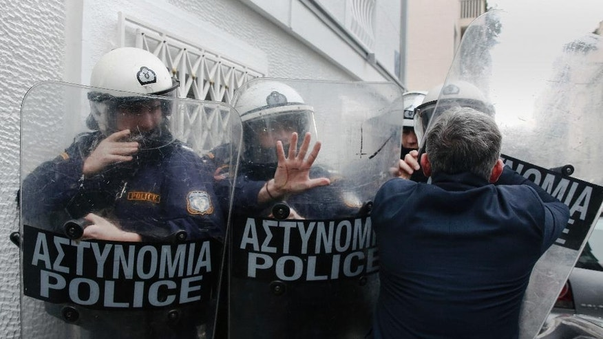 Michalis Giannakos, president of the National Panhellenic Federation of Public Hospital Employees, tries to cross a police formation during a protest against government's policies on health issues in Athens, Wednesday, January 25, 2017. Greece's left-wing government says it is willing to extend an automatic austerity mechanism for one additional year in an effort to break the deadlock on current bailout negotiations. (AP Photo/Yorgos Karahalis)