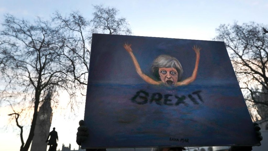 Artist Kaya Mar holds a painting near Parliament in London, Tuesday, Jan. 24, 2017. Lead plaintiff Gina Miller says British Supreme Court ruling provides the legal foundation to trigger Brexit. (AP Photo/Kirsty Wigglesworth)