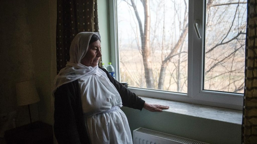 In this photo taken Wednesday, Dec. 21, 2016, a Yazidi refugee woman looks out of a window of a hotel room in the northern Greek village of Agios Athanasios, near Thessaloniki city. Portugal has offered to take in several hundred of the 2,500 Yazidi refugees living in Greece, arguing that the mistreated religious minority merits special protection. (AP Photo/Giannis Papanikos)