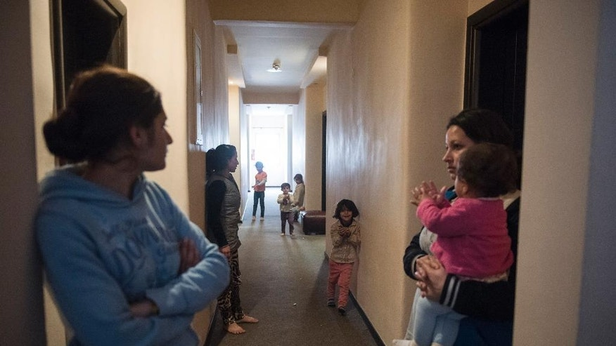In this photo taken Wednesday, Dec. 21, 2016, Yazidi refugees are pictured at the corridor of a hotel, in the northern Greek village of Agios Athanasios, near Thessaloniki city. Portugal has offered to take in several hundred of the 2,500 Yazidi refugees living in Greece, arguing that the mistreated religious minority merits special protection. (AP Photo/Giannis Papanikos)