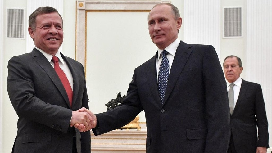 Russian President Vladimir Putin, right, shakes hands with Jordan's King Abdullah II during their meeting in the Kremlin in Moscow, Russia, Wednesday, Jan. 25, 2017. In the back is Russian Foreign Minister Sergey Lavrov. (Alexander Nemenov/Pool Photo via AP)