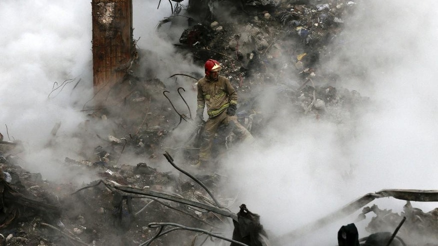 A firefighter works to remove debris from the Plasco building, which collapsed after being engulfed by a fire on Thursday, in central Tehran, Iran, Tuesday, Jan. 24, 2017. Rescue teams are trying to reach missing firefighters, victims and looking for survivors believed to be under the rubble of the Plasco high-rise commercial building. (AP Photo/Vahid Salemi)