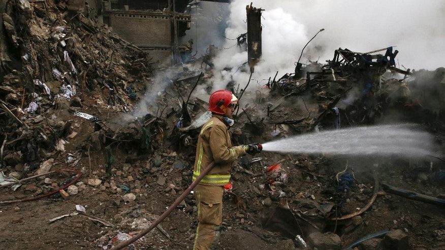 A firefighter sprays water on debris from the Plasco building, which collapsed after being engulfed by a fire on Thursday, in central Tehran, Iran, Tuesday, Jan. 24, 2017. Rescue teams are trying to reach missing firefighters, victims and looking for survivors believed to be under the rubble of the Plasco high-rise commercial building. (AP Photo/Vahid Salemi)