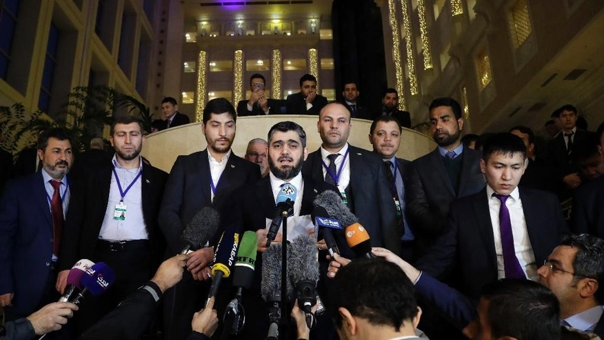 Mohammed Alloush, head of a Syrian opposition delegation, center, speaks to the media after the talks on Syrian peace in Astana, Kazakhstan, Tuesday, Jan. 24, 2017. Russia, Iran and Turkey _ sponsors of talks in Kazakhstan between Syria and rebel factions _ pledged Tuesday to consolidate the country's nearly month-old cease-fire and set up a three-way mechanism to ensure compliance of all sides. (AP Photo/Sergei Grits)