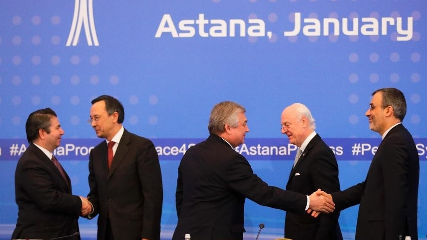 Turkish Foreign Ministry Deputy Undersecretary Sedat Onal, left, and Kazakh Foreign Minister Kairat Abdrakhmanov shake hands, as Russia's special envoy on Syria Alexander Lavrentiev and Iran's Deputy Foreign Minister Hossein Jaber Ansari, right, shake hands and UN Syria envoy Staffan de Mistura stand after the final statement following the talks on Syrian peace in Astana, Kazakhstan, Tuesday, Jan. 24, 2017. Russia, Iran and Turkey _ sponsors of talks in Kazakhstan between Syria and rebel factions _ pledged Tuesday to consolidate the country's nearly month-old cease-fire and set up a three-way mechanism to ensure compliance of all sides. (AP Photo/Sergei Grits)