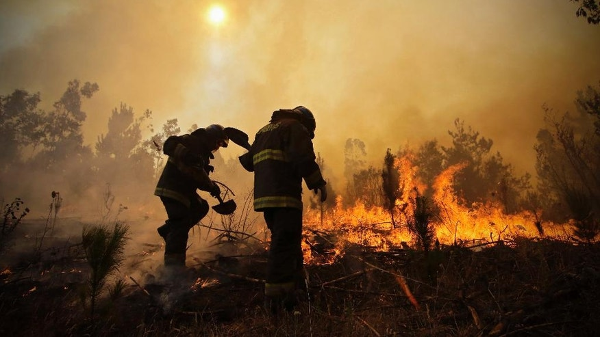 Firefighters dig trenches in a effort to stop the advancement of a forest fire in Hualañe, a community in Concepcion, Chile, Wednesday, Jan. 25, 2017. The worst forest fires in Chile's history were uncontrolled on Wednesday, killing a firefighter and two policemen caught in the flames as they tried to help families in rural communities, authorities said. (Alejandro Zoñez/Aton via AP) NO PUBLICAR EN CHILE