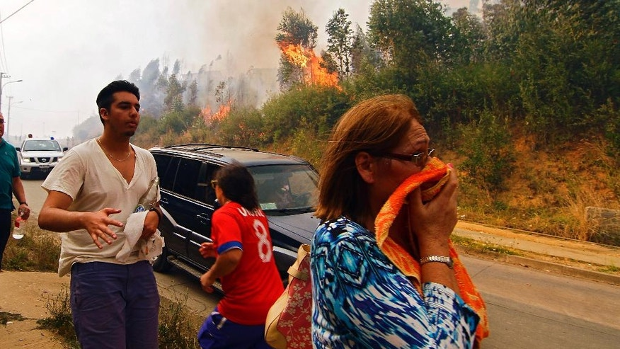 People react to the advancement of a forest fire in Hualañe, a community in Concepcion, Chile, Wednesday, Jan. 25, 2017. The worst forest fires in Chile's history were uncontrolled on Wednesday, killing a firefighter and two policemen caught in the flames as they tried to help families in rural communities, authorities said. (Alejandro Zoñez/Aton via AP) NO PUBLICAR EN CHILE