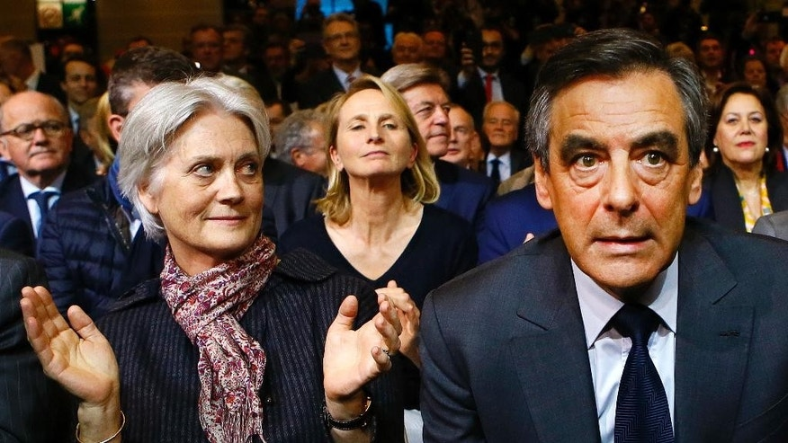 FILE - In this Friday, Nov. 25, 2016 file picture, Francois Fillon, a candidate in Sunday's primary runoff to select a conservative candidate for the French presidential election, sits with his wife Penelope, left, during a rally in Paris, France. French presidential hopeful Francois Fillon's so far smooth campaign has hit its first hurdle after claims that his wife was paid about half a million euro with parliamentary funds emerged. (AP Photo/Francois Mori, File)