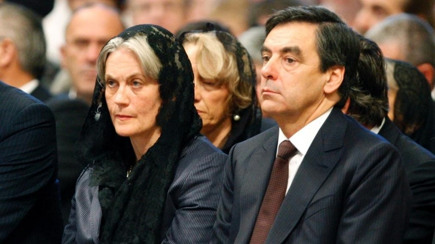 FILE - In this Sunday, Oct. 11, 2009 file picture, France's Prime Minister Francois Fillon and his wife Penelope attend a canonization ceremony led by Pope Benedict XVI in St. Peter's Basilica at the Vatican. French presidential hopeful Francois Fillon's so far smooth campaign has hit its first hurdle after claims that his wife was paid about half a million euro with parliamentary funds emerged. (AP Photo/Alessandra Tarantino, File)