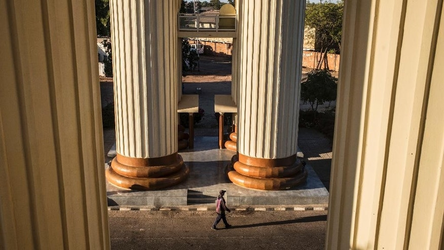 A man walks under the commemorative arch in Banjul, Gambia, Wednesday Jan. 25, 2017. Gambia's new President Adama Barrow will arrive in the country on Thursday, a week after he was sworn into office in neighboring Senegal, officials with the new government confirmed Wednesday. (AP Photo/Sylvain Cherkaoui)
