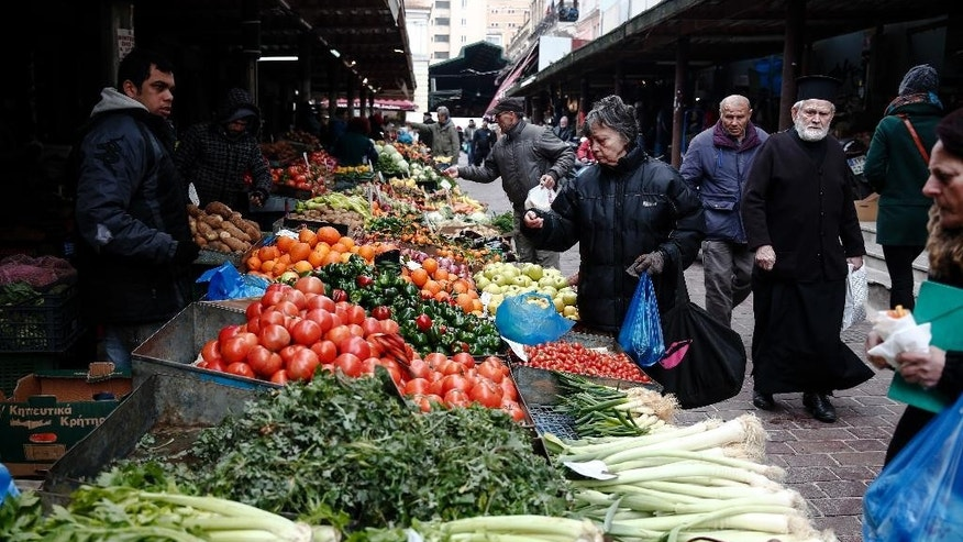 Consumers buy groceries at a main food market of Athens, Thursday, Jan. 26, 2017. Greece's prime minister on Wednesday marked two years in office, as talks with bailout lenders remain at an impasse. (AP Photo/Yorgos Karahalis)
