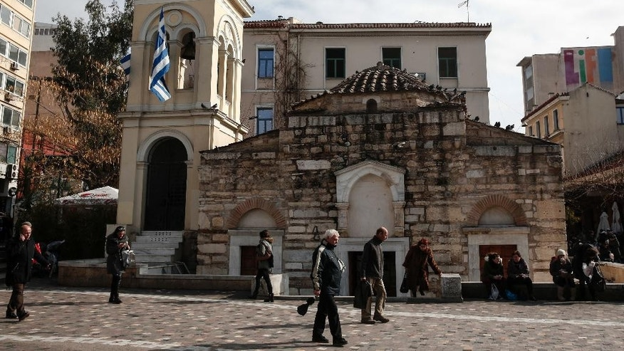 People make their way in front of an Orthodox church at a main square of Athens, Thursday, Jan. 26, 2017. Greece's prime minister on Wednesday marked two years in office, as talks with bailout lenders remain at an impasse. (AP Photo/Yorgos Karahalis)