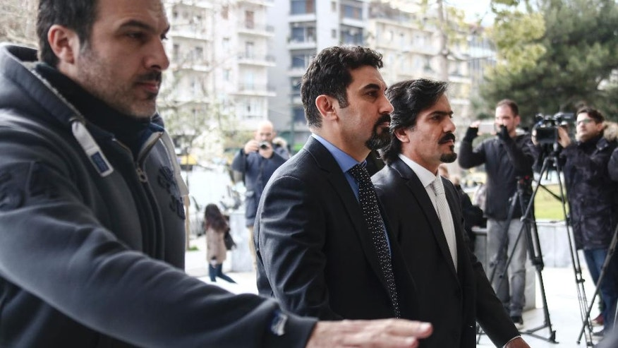 Turkish military officers, right, escorted by Greek police officer arrive at the Supreme Court in Athens,Thursday, Jan. 26, 2017. A group of Turkish servicemen who fled to Greece in a military helicopter after last year's failed coup have appeared at Greece's Supreme Court in a closely watched extradition hearing. (AP Photo/Yorgos Karahalis)