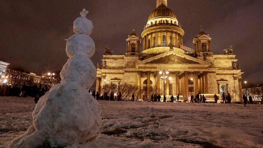 FILE In this Friday, Jan. 13, 2017 file photo a snowman stands in front of the St. Isaac's Cathedral in St.Petersburg, Russia. The Hermitage Museum Director Mikhail Piotrovsky  has urged the head of the Russian Orthodox Church in a letter Wednesday Jan. 25 2017,  to recall its bid for a landmark St. Petersburg cathedral. Several hundred people have rallied outside the iconic St. Isaac's Cathedral earlier this month, fearing that its transferal from the city to the church may inhibit public access. (AP Photo/Dmitri Lovetsky, File)