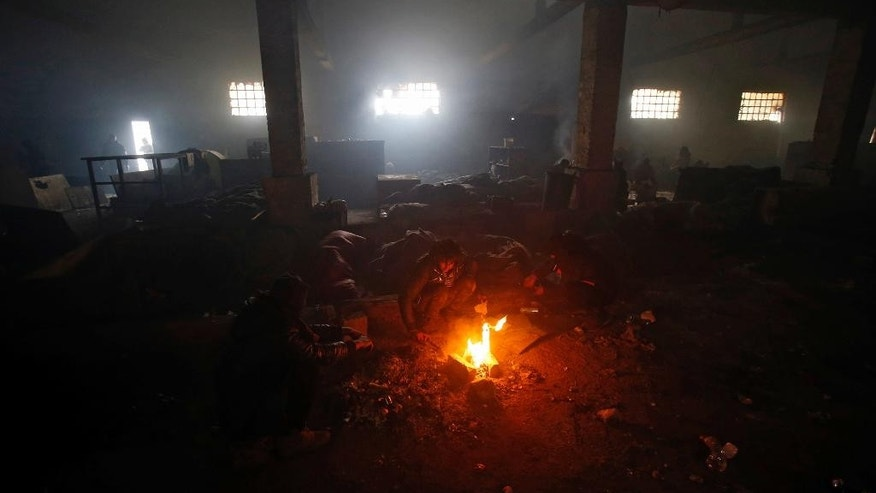 Migrants warm themselves by the fire in an abandoned warehouse in Belgrade, Serbia, Wednesday, Jan. 25, 2017. Hundreds of migrants have been sleeping rough in freezing conditions in downtown Belgrade looking for ways to cross the heavily guarded EU borders. (AP Photo/Darko Vojinovic)