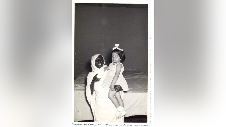 "In this undated handout photo, provided by Tales of Jewish Sudan, a young Regina Cohen, is held by her nanny in Khartoum, Sudan. Sudan's Jewish community grew to about 1,000 people at its peak, with most living in the big cities of Khartoum, Omdurman, Khartoum North and Wad Madani. Many met regularly at Khartoum's synagogue or the city's Jewish Recreational Club. ""We used to go to the synagogue on the sabbath, celebrate New Year, and if someone was missing, someone would ask,"" remembers Regina Cohen, 70, who left Sudan in 1966 and also lives in Israel. (Photo courtesy of Regina Cohen, Tales of Jewish Sudan, via AP)"
