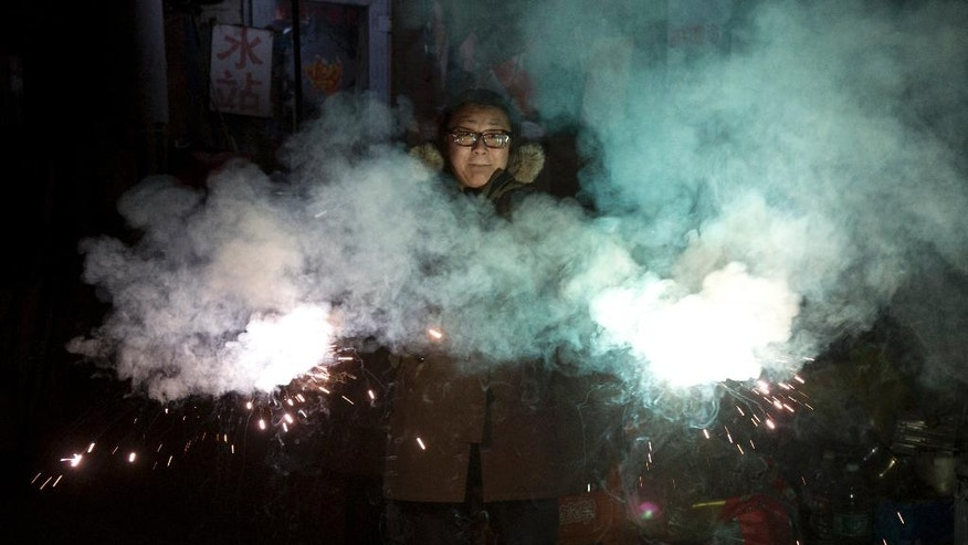 A resident lets off sparklers on the eve of Lunar New Year in Beijing, China, Friday, Jan. 27, 2017. Chinese worldwide celebrate the Year of the Rooster on Jan 28, 2017 with family reunions and fireworks. (AP Photo/Ng Han Guan)