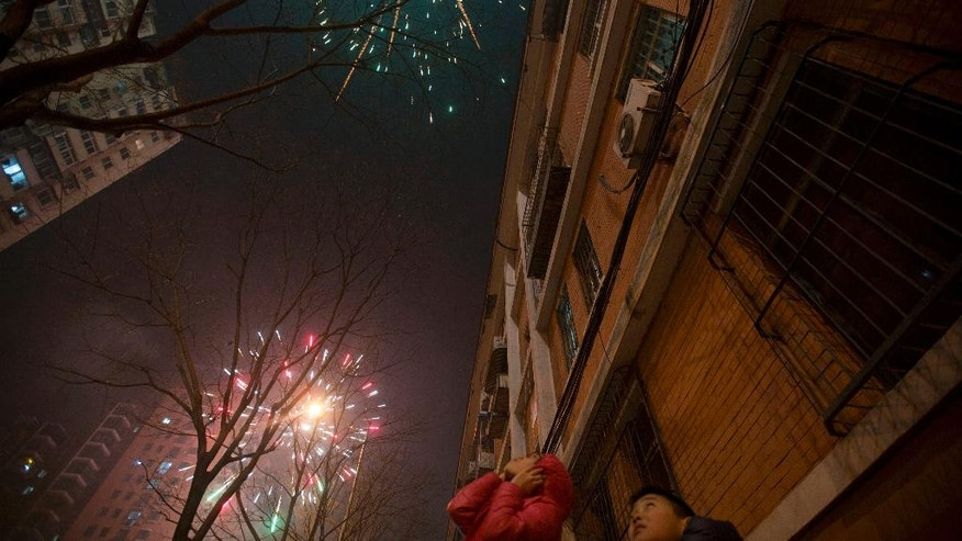 A Chinese girl covers her ears as residents set off fireworks on the eve of Lunar New Year in Beijing, China, Friday, Jan. 27, 2017. Chinese worldwide celebrate the Year of the Rooster on Jan 28, 2017 with family reunions and fireworks. (AP Photo/Ng Han Guan)