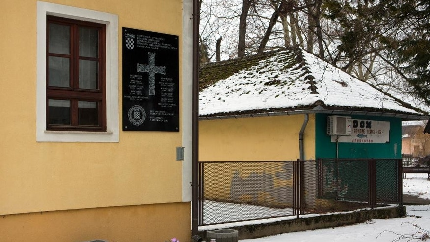 In this Jan. 26, 2017 photo, the plaque containing a pro-nazi salute honoring Croatian fighters killed during the 1990s' war is put on a wall of a building in Jasenovac, near the site of wartime death camp in Croatia. Croatia's Jewish groups have boycotted the official Holocaust Remembrance Day ceremonies saying the conservative government is not doing enough to curb pro-Nazi sentiments in the country. (AP Photo/Darko Bandic)