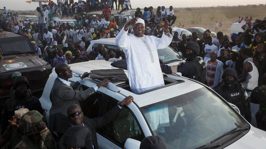 Gambian President Adama Barrow waves as he rides his motorcade through crowds of hundreds of thousands after arriving at Banjul airport in Gambia, Thursday Jan. 26, 2017, after flying in from Dakar, Senegal. Gambia's new president has finally arrived in the country, a week after taking the oath of office abroad amid a whirlwind political crisis. Here's a look at the tumble of events that led to Adama Barrow's return — and the exile of the country's longtime leader. (AP Photo/Jerome Delay)