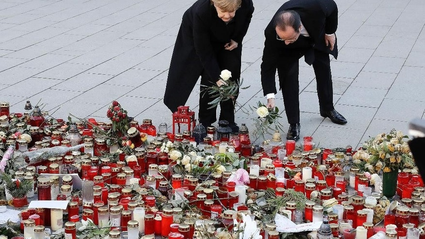 German Chancellor Angela Merkel,left, and the President of France, Francois Hollande, lay down flowers to commemorate the victims of a terror attack on the Breitscheidplatz last December in Berlin, Germany, Friday, Jan. 27, 2017. (AP Photo/Michael Sohn)