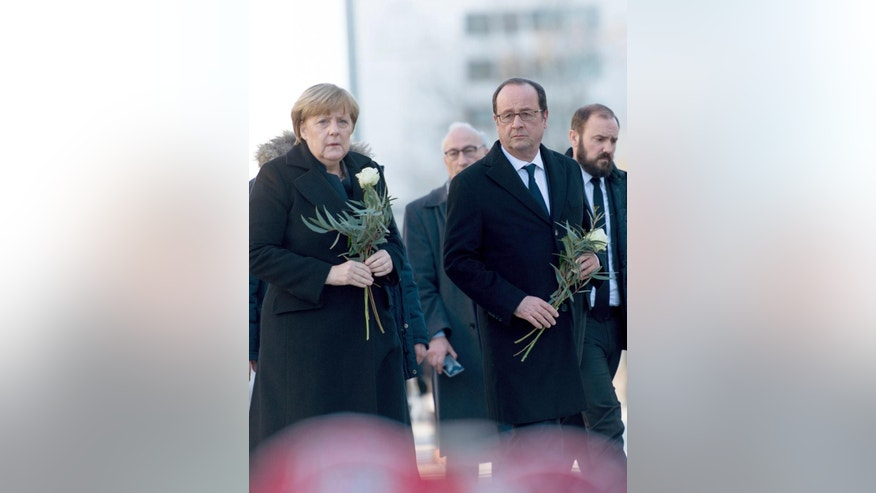 German Chancellor Angela Merkel,left, and French President Francois Hollande visit the site of the terror attack  to lay flowers at Breitscheidplatz in Berlin, Germany, Friday, Jan. 27, 2017.( Monika Skolimowska/dpa via AP)