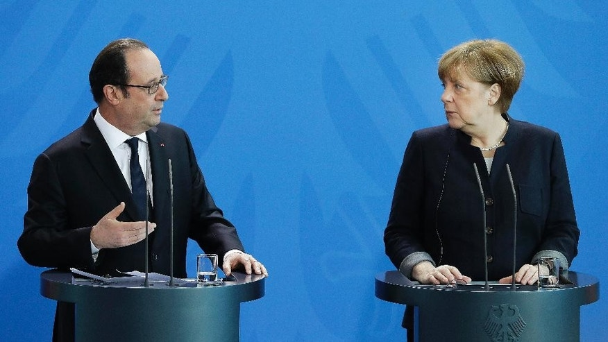 German Chancellor Angela Merkel, right, and the President of France, Francois Hollande, left, address the media during a joint statement as part of a meeting at the chancellery in Berlin, Germany, Friday, Jan. 27, 2017. (AP Photo/Michael Sohn)