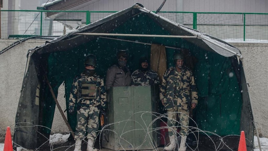 Indian paramilitary soldiers take shelter from snow inside a tent as they stand guard on the eve of the Republic Day in Srinagar, Indian controlled Kashmir, Wednesday, Jan. 25, 2017. Four members of a family and an Indian soldier were killed Wednesday when they were buried by two separate avalanches in the Himalayan region of Kashmir, officials said. (AP Photo/Dar Yasin)