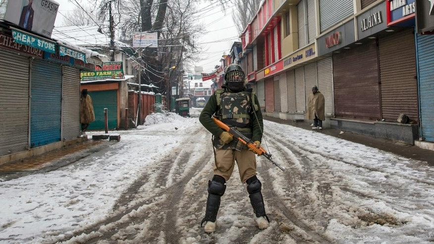 An Indian paramilitary soldier stands guard at a closed market as it snows during a general strike in Srinagar, Indian controlled Kashmir, Thursday, Jan. 26, 2017. Shops remained closed Thursday as separatists called for a general strike in the Indian-controlled portion of the disputed Kashmir region on India's Republic Day. (AP Photo/Dar Yasin)