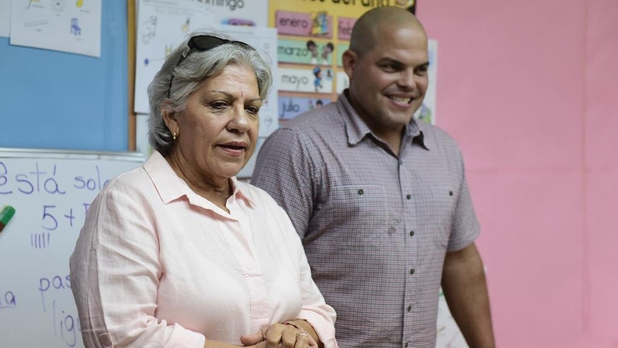 Eva Torres stands next to her son Former Major League Baseball player Ivan 'Pudge' Rodriguez, as he is welcomed in his hometown school, José Gualberto Padilla Elementary, in Vega Baja, Puerto Rico, Friday, Jan. 27, 2017.  The Puerto Rican catcher is visiting his native island to celebrate his election to the Baseball Hall of Fame last week. Rodriguez is the fourth native Puerto Rican in the hall and became the youngest inductee at 45 years old. (AP Photo/Carlos Giusti)