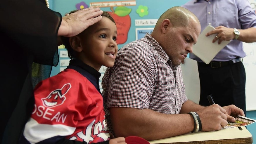 Former Major League Baseball player Ivan 'Pudge' Rodriguez, who was received in his hometown school, José Gualberto Padilla Elementary, autographs a poster in Vega Baja, Puerto Rico, Friday, Jan. 27, 2017.  The Puerto Rican catcher is visiting his native island to celebrate his election to the Baseball Hall of Fame last week. Rodriguez is the fourth native Puerto Rican in the hall and became the youngest inductee at 45 years old. (AP Photo/Carlos Giusti)