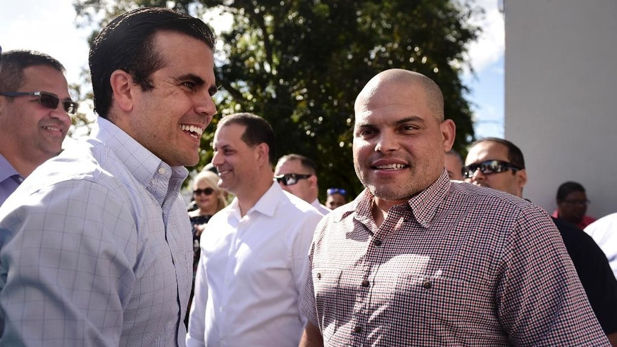 Puerto Rico Gov. Ricardo Rossello, left, greets former Major League Baseball player Ivan 'Pudge' Rodriguez, in his hometown Vega Baja, Puerto Rico, Friday, Jan. 27, 2017.  The Puerto Rican catcher is visiting his native island to celebrate his election to the Baseball Hall of Fame. Rodriguez is the fourth native Puerto Rican in the hall and became the youngest inductee at 45 years old. (AP Photo/Carlos Giusti)
