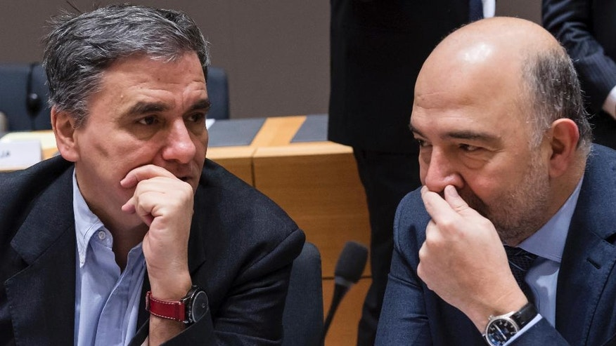 European Commissioner for Economic and Financial Affairs Pierre Moscovici, right, talks with Greece's Finance Minister Euclid Tsakalotos during a round table meeting of EU finance ministers at the EU Council building in Brussels on Friday, Jan. 27, 2017. (AP Photo/Geert Vanden Wijngaert)
