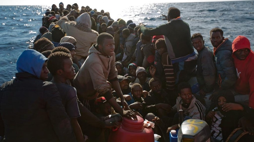 Sub-Saharan migrants wait in a crowded rubber boat to be rescued by members of Proactive Open Arms NGO, in the Mediterranean sea, about 22 miles north of Zumarah, Libya, on Friday, Jan. 27, 2017. Tens of thousands of people seeking better lives are expected to trek across deserts and board unseaworthy boats in war-torn Libya this year in a desperate effort to reach European shores by way of Italy. (AP Photo/Emilio Morenatti)