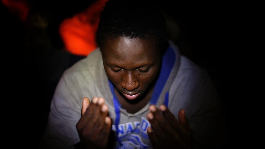 A Sub-Saharan migrant prays on the deck of the Golfo Azzurro boat after being rescued from a rubber boat by members of Proactive Open Arms NGO, in the Mediterranean sea, about 24 miles north of Sabratha, Libya, on Friday, Jan. 27, 2017. Tens of thousands of people seeking better lives are expected to trek across deserts and board unseaworthy boats in war-torn Libya this year in a desperate effort to reach European shores by way of Italy. (AP Photo/Emilio Morenatti)