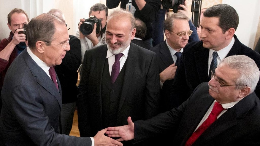 Russian Foreign Minister Sergey Lavrov, left, shakes hands with Syria's opposition members in Moscow, Russia, Friday, Jan. 27, 2017. Lavrov said at the start of his Friday's meeting that the negotiations previously set for Feb. 8 have been postponed until the end of the month. He didn't elaborate on reasons behind the delay. (AP Photo/Pavel Golovkin)