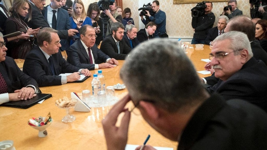 Russian Foreign Minister Sergey Lavrov, third from left, attends a meeting with Syria's opposition members in Moscow, Russia, Friday, Jan. 27, 2017. Lavrov said at the start of his Friday's meeting that the negotiations previously set for Feb. 8 have been postponed until the end of the month. He didn't elaborate on reasons behind the delay. (AP Photo/Pavel Golovkin)