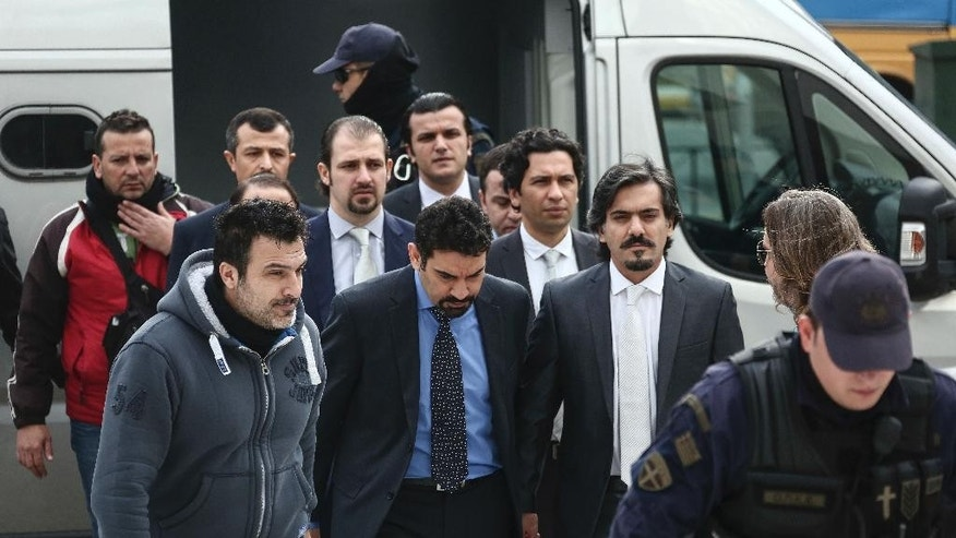 Turkish military officers, center, escorted by Greek police officers, arrive at the Supreme Court in Athens,Thursday, Jan. 26, 2017. A group of Turkish servicemen who fled to Greece in a military helicopter after last year's failed coup have appeared at Greece's Supreme Court in a closely watched extradition hearing. (AP Photo/Yorgos Karahalis)